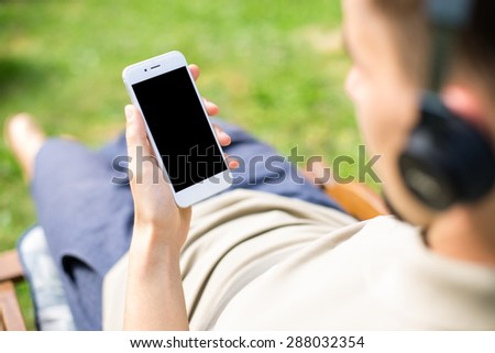 Man using smartphone with blank screen while listen to the music. - stock photo
