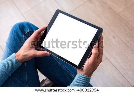 Man using tablet computer while sitting on a wooden floor. View from above. Clipping path included. - stock photo