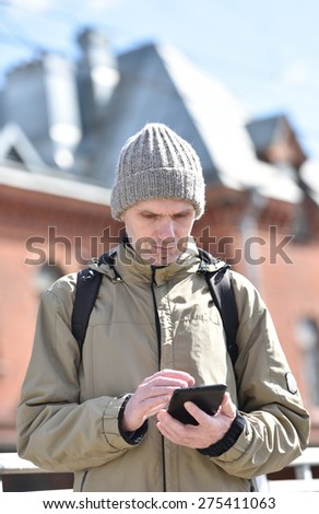 Man using tablet outdoors in a sunny spring day