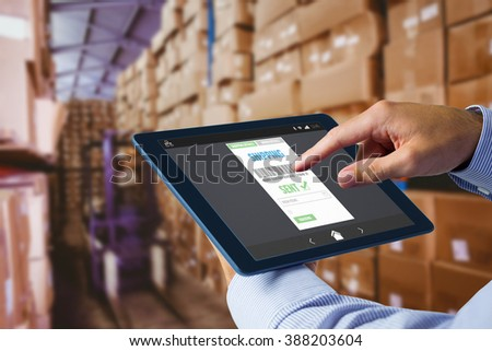 Man using tablet pc against forklift in large warehouse - stock photo
