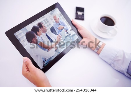 Man using tablet pc against group of business people brainstorming together - stock photo