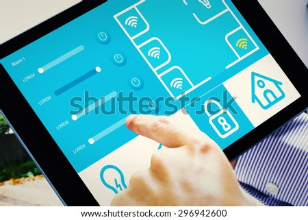 Man using tablet pc against home automation system