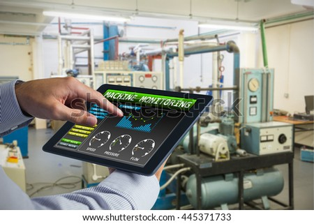 Man using tablet pc against machinery in empty illuminated workshop