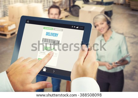 Man using tablet pc against manager walking with her colleague pulling trolleys - stock photo