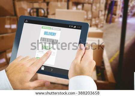 Man using tablet pc against warehouse with cardboard boxes - stock photo
