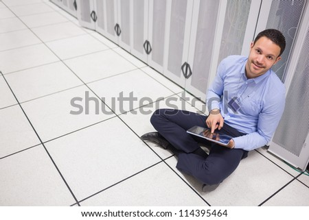 Man using tablet pc sitting beside servers in data center - stock photo
