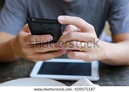 man using the digital tablet and phone working in living room,  Internet of things lifestyle with wireless communication and internet with smartphone.