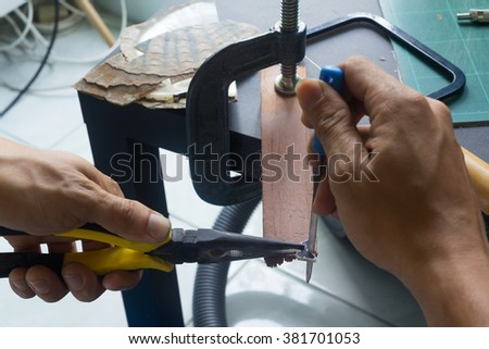 Man using tools perforate shell/handicrafts in workshop /accessories from pearl shell and abalone