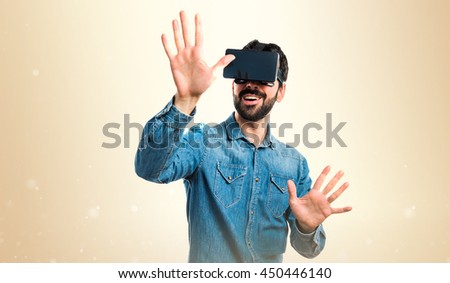 Man using VR glasses touching on transparent screen over ocher background - stock photo
