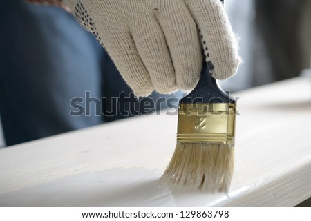 Man varnishing the wooden plank - stock photo