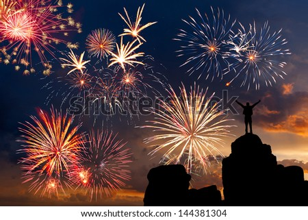 Man view from top of a mountain on beautiful fireworks in the evening sky with majestic clouds - stock photo