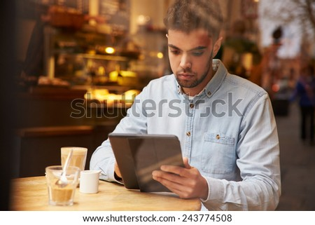 Man Viewed Through Window Of Caf�¢?? Using Digital Tablet - stock photo