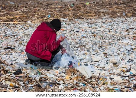 Man volunteer collecting garbage on beach - stock photo