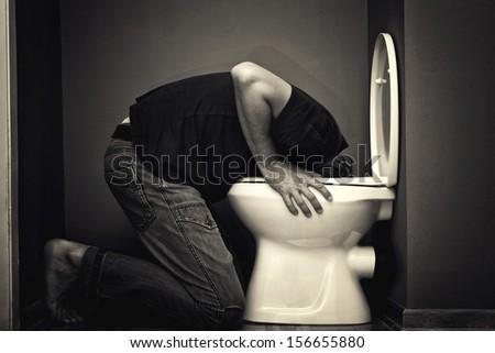 Man vomiting in toilet bowl - stock photo