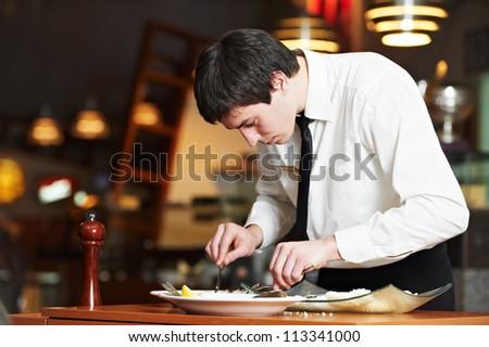 man waiter in uniform preparing fish food on plates at restaurant - stock photo