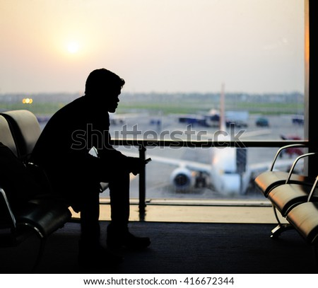 Man waiting for a flight at the airport - stock photo