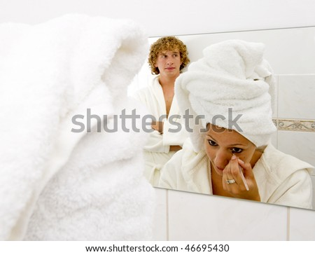 Man waiting for his girlfriend to finish doing her makeup, so he can get in front of the mirror - stock photo
