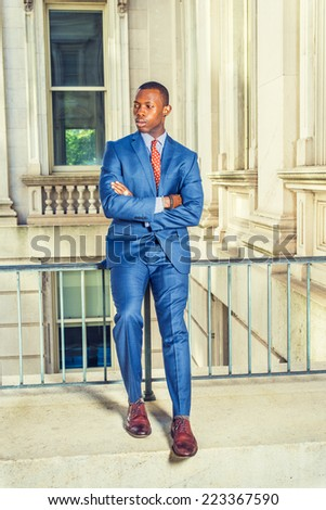 Man Waiting for You. Dressing formally in blue suit, patterned undershirt, tie, leather shoes, haircut, crossing arms, a young black businessman is sitting on railing in office building, relaxing, - stock photo