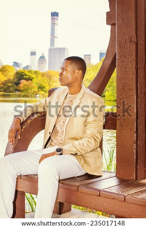 Man Waiting for You. Dressing in cream blazer, collarless sweater, white pants, wearing a wristwatch, a young black guy is sitting by a lake in a big city, relaxing, thinking. - stock photo