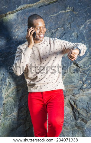 Man Waiting for You. Dressing in cream, patterned, collarless sweater, red pants, wearing wristwatch, a young guy is standing by rocks, smiling, making a phone call, raising arm, looking at watch,  - stock photo