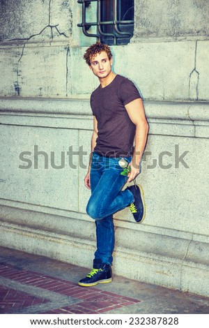 Man Waiting for You. Wearing dark brown T shirt, blue jeans, black sneakers, a young sexy guy with curly hair is standing against wall by window, holding a white rose, bending a leg, looking away. - stock photo