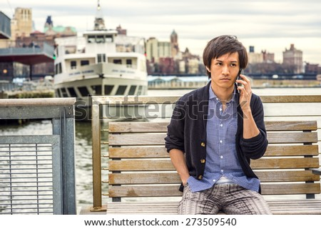 Man waiting for you. Wearing patterned shirt, black sweater, casual pants, a young Japanese guy sitting on chair by river, making a phone call. An old big city outline, a boat, on background. - stock photo