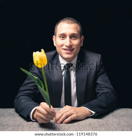 Man waiting his girlfriend at a restaurant with yellow flower.