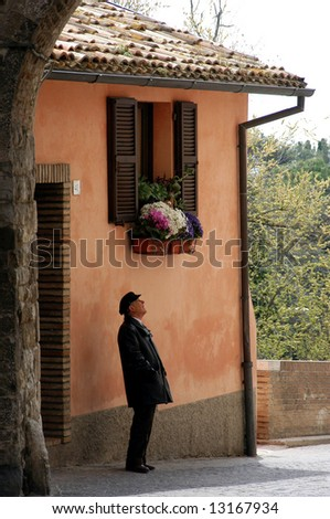 man waiting under a window in sirolo italy - stock photo