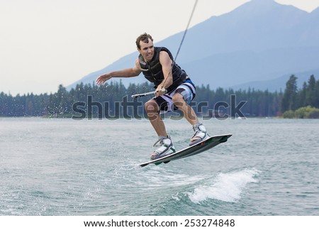 Man wakeboarding on a beautiful mountain lake - stock photo