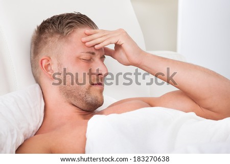 Man waking up with a nasty headache from overindulgence or illness wincing in pain and raising his hands to his head - stock photo
