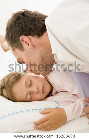Man waking young girl in bed with kiss