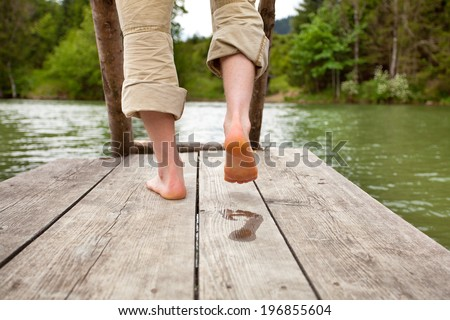 man walk barefoot feet on old wooden Pier on a lake in bavarian alps, he leaves a wet footprint
