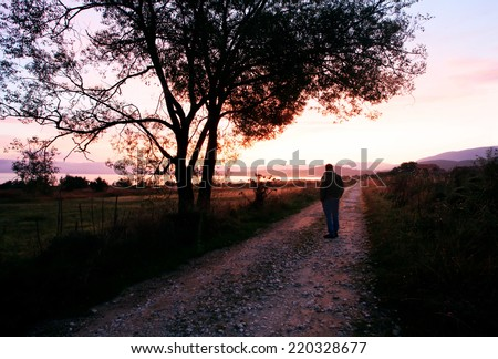 man walk on dirt road near lake, calm red sunrise on low light, long exposure with smooth clouds