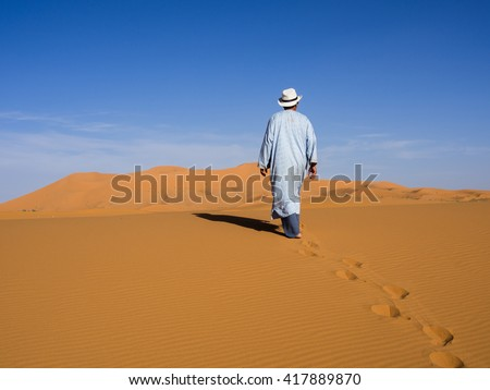 Man walking alone among the sand dunes of the Sahara desert. Best of Morocco - stock photo