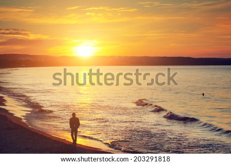 Man walking alone on the beach at sunset. Calm sea with rippling waves. - stock photo