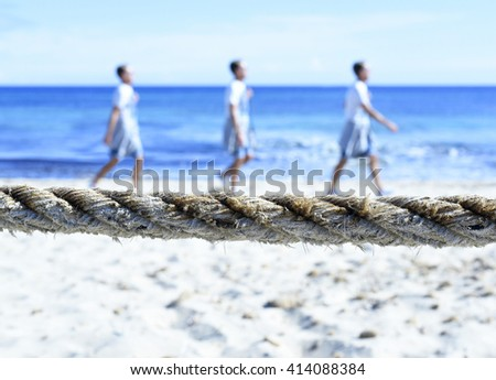 man walking along the beach. Serial exposure of a person walking on a rope. - stock photo