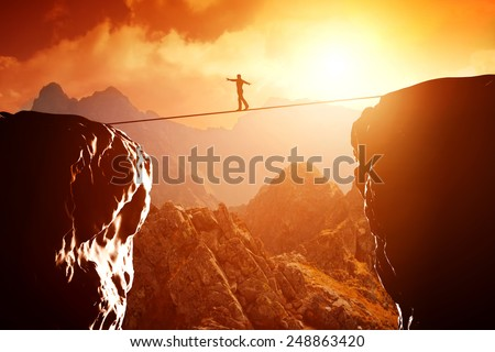 Man walking and balancing on rope over precipice in mountains at sunset. Concept of business, risk taking, challenge, concentration. - stock photo