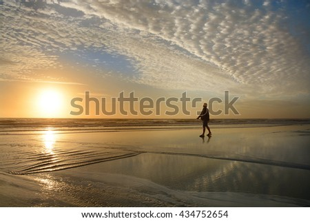 Man walking and relaxing on beautiful the beach at sunrise. Beautiful cloudy sky reflected on the beach. Jacksonville, Florida, USA. - stock photo