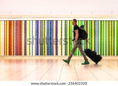Man walking at international airport with suitcase and backpack - Concept of alternative lifestyle traveling around the world - Young hipster traveler in hurry for airplane boarding after check in - stock photo