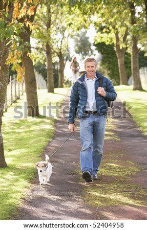 Man Walking Dog Outdoors In Autumn Park