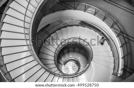 Man walking down at spiral staircase. Image with black & white and noise effect.