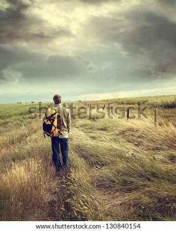 Man walking down country road on the prairies - stock photo