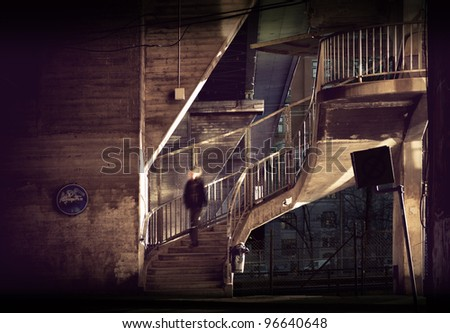 Man walking down staircase in run down area