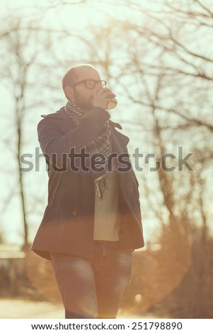 Man walking down the park and drinking coffee - stock photo