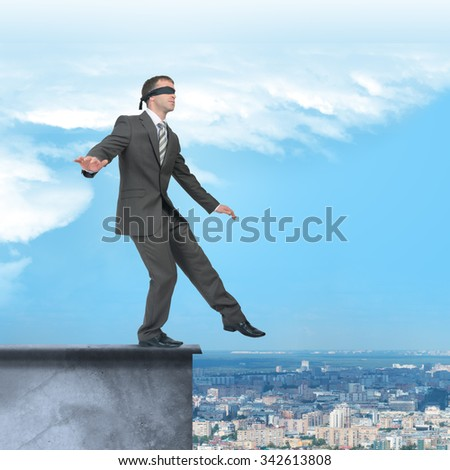 Man walking from edge of building roof with band on his eyes