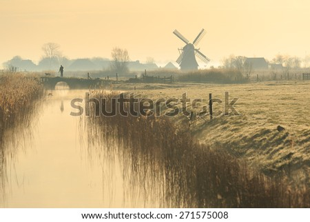 Man walking his dog near a windmill in the Dutch countryside on a foggy, spring morning.