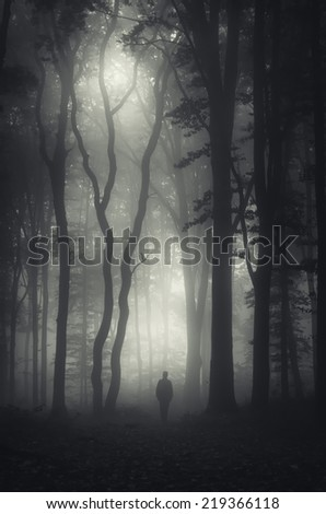 man walking in mysterious dark forest - stock photo