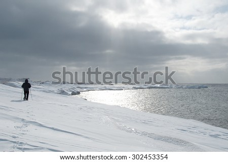 Man walking in snowshoes on snow at the seaside - stock photo
