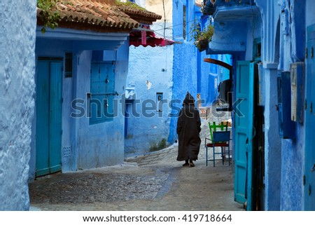 Man walking in the blue medina of Chefchaouen, Morocco - stock photo
