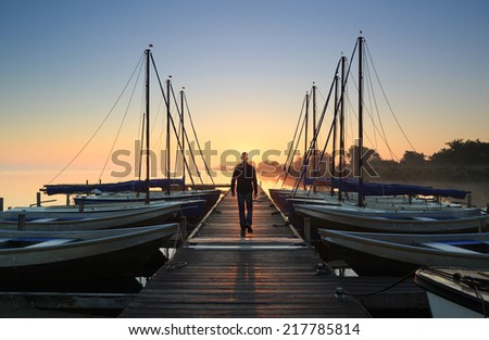 Man walking on a jetty in a marina during a foggy, autumn sunrise at a lake. - stock photo